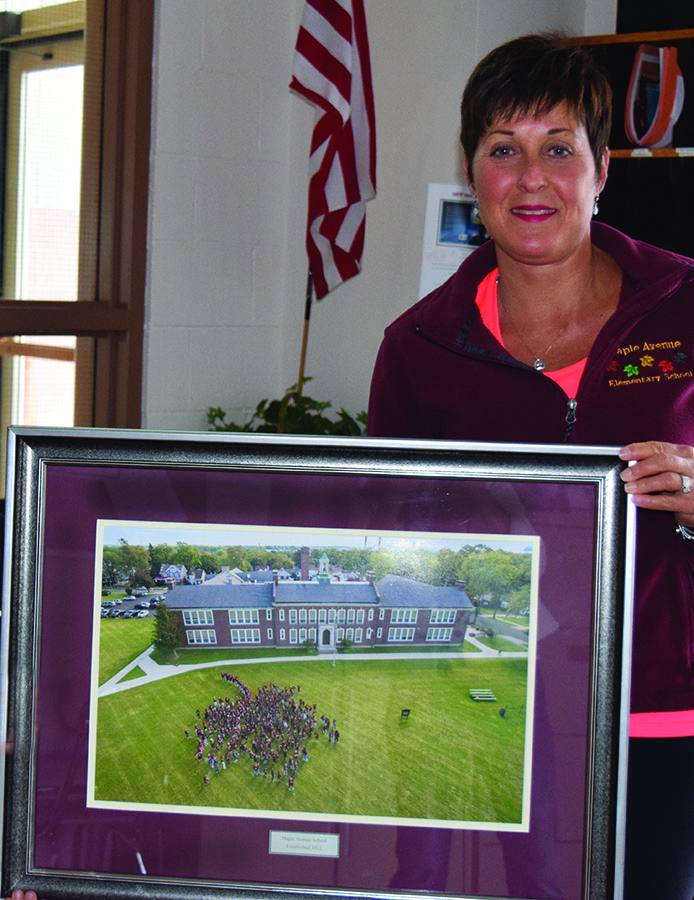Mrs. Chille-Zafuto with photo of Maple Avenue School